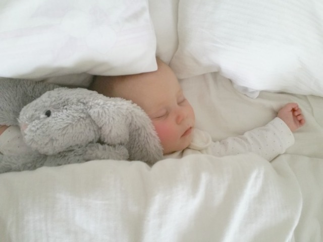 six month old baby sleeping in bed