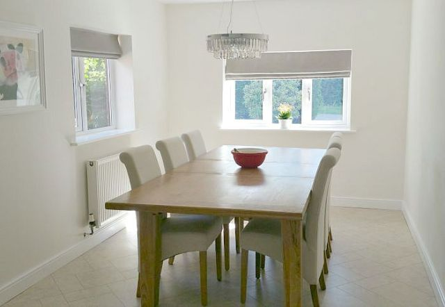 Traditional oak eight-seater dining table with white high-back chairs